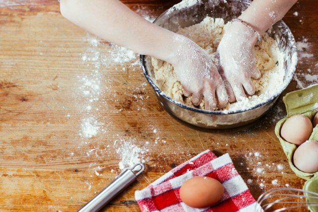 A woman's hands covered in flour kneading dough in a bowl in preparation for baking.