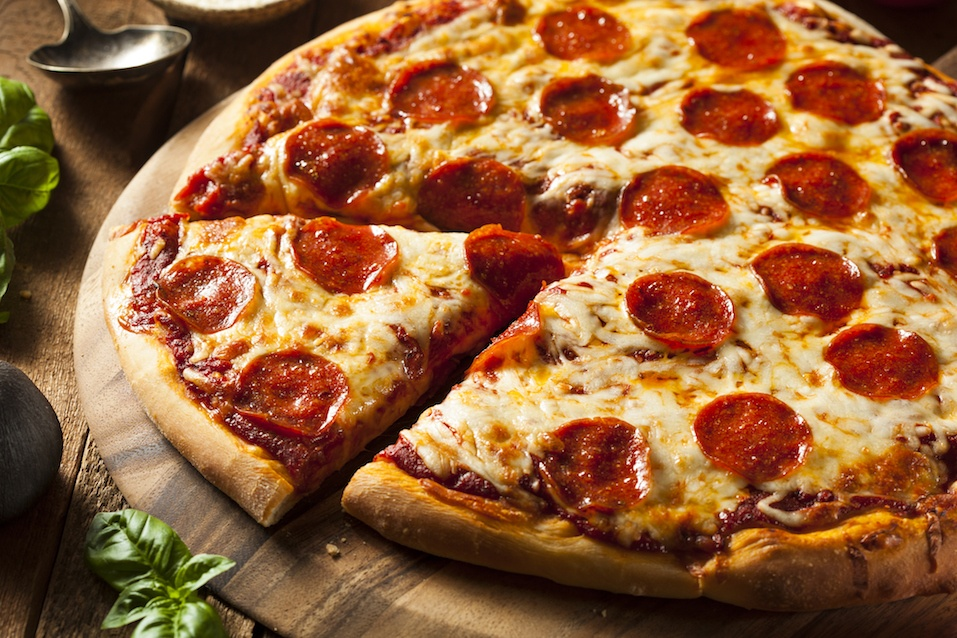 Cheesy pepperoni pizza with one section cut into a slice.