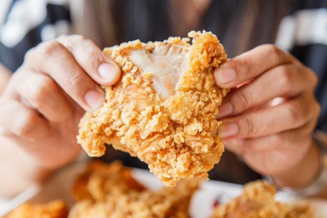 Two hands holding a piece of crispy fried chicken.