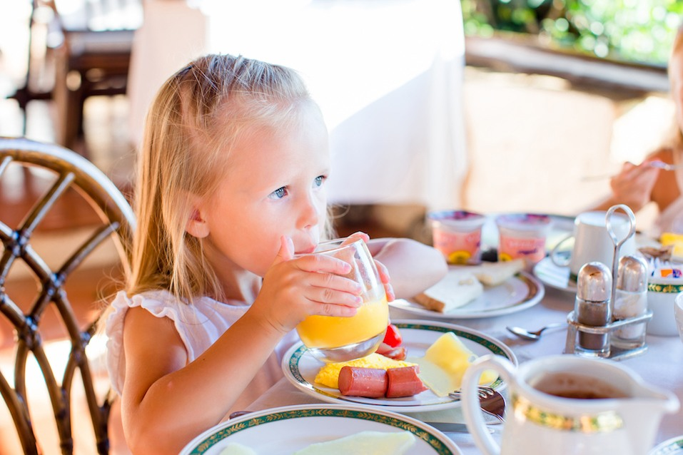 girl drinking orange juice at breakfast