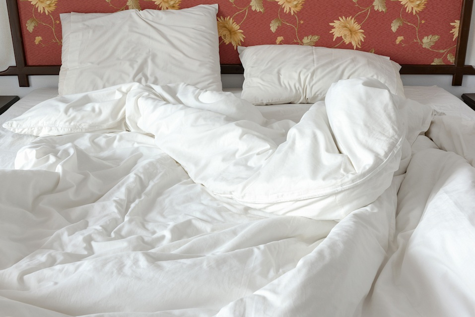 untidy bed with a white crumpled blanket