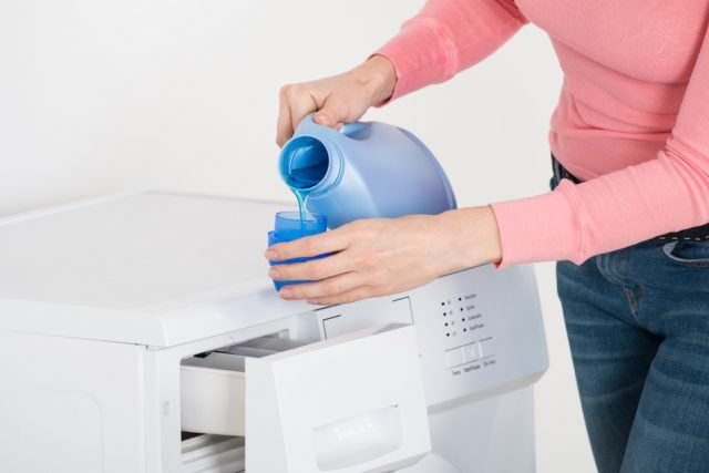 Female Hand Pouring Detergent In The Blue Bottle Cap