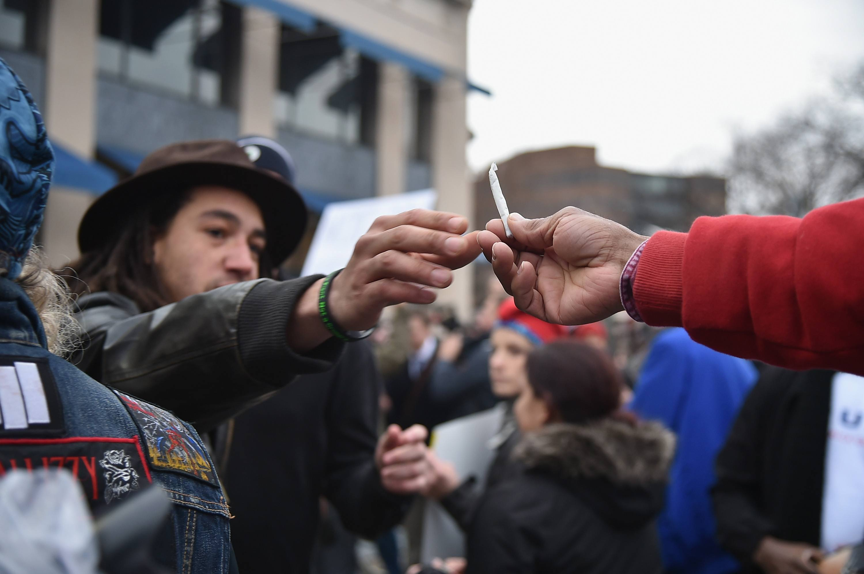 Men pass a joint at a pro-pot rally
