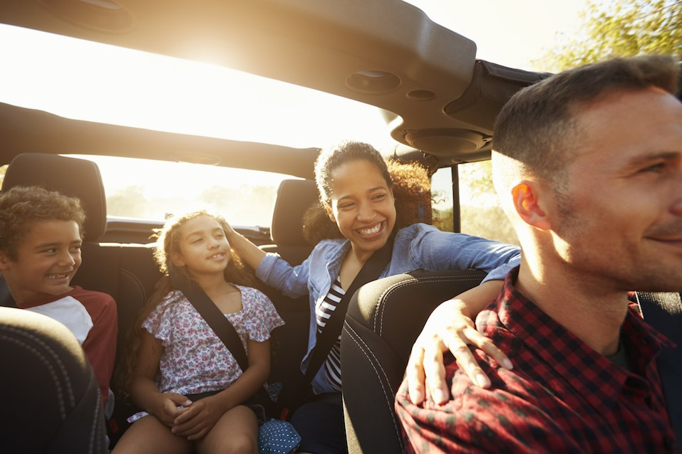 Happy family on a road trip in car