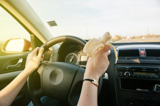 A woman eats a banana while driving.