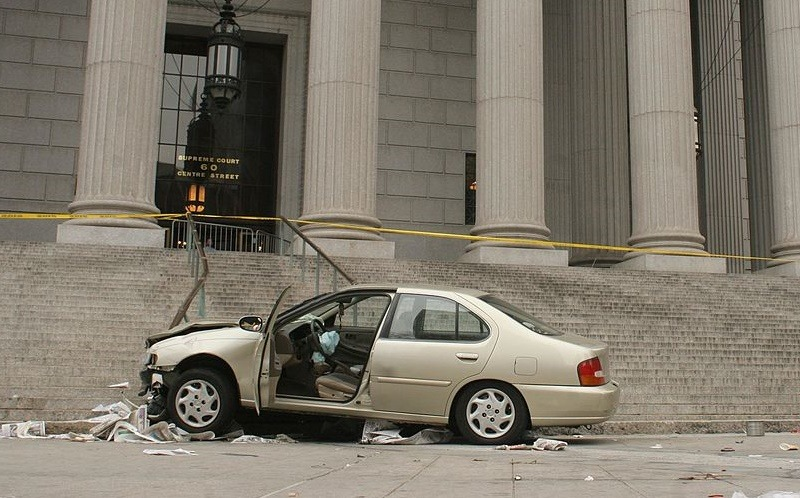NEW YORK - APRIL 11: Emergency tape surrounds the scene where a car that crashed into the base of the steps of the state Supreme Court building in downtown Manhattan April 11, 2008 in New York City. The car jumped the sidewalk, smashed into a coffee cart and went up several steps, pinning a man in the process. At least six people were injured.