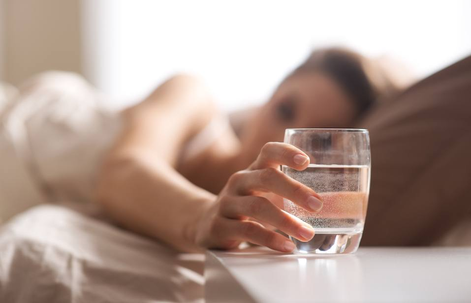 woman reaching for her glass of water while in her bed