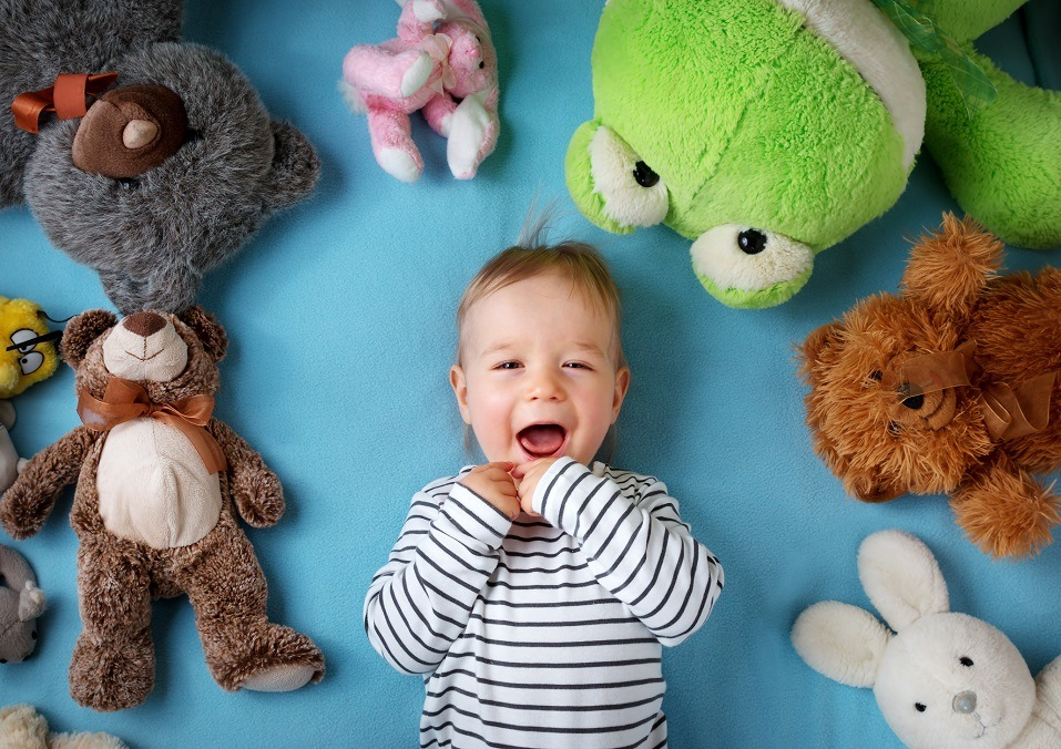 one year old boy lying with many plush toys
