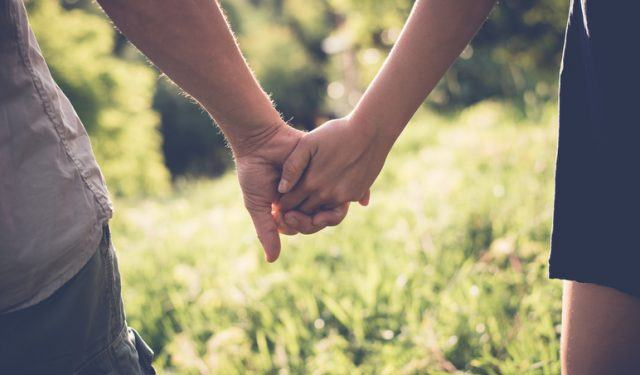 Two people hold hands as they walk through a field.