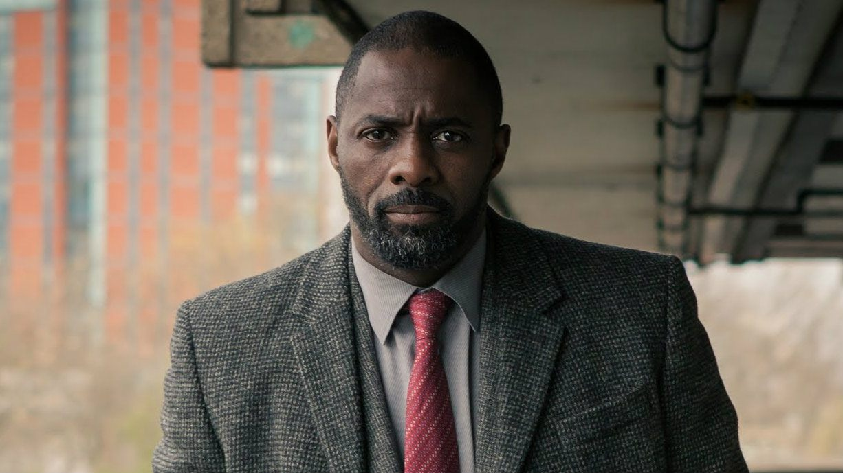 Idris Elba in a suit walking and looking at the camera in Luther