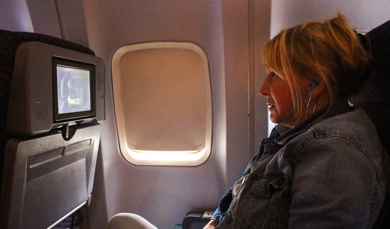 Woman watches inflight entertainment
