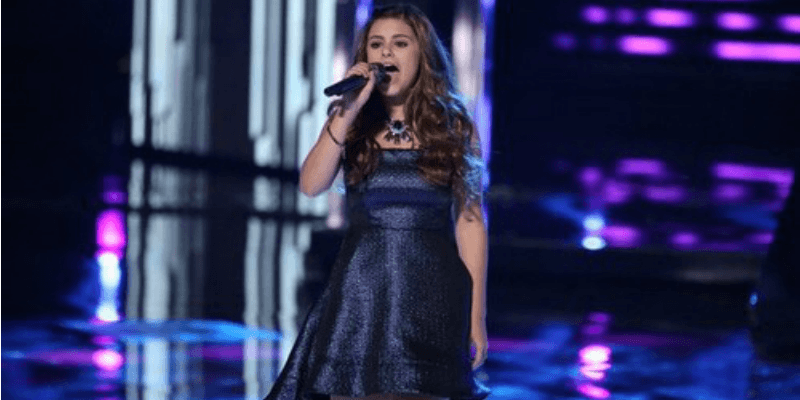 Jacquie Lee is singing in a blue dress on The Voice.