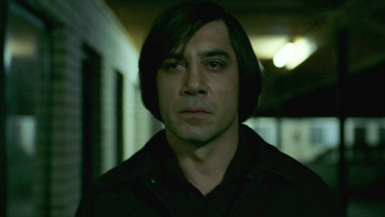 Javier Bardem as Anton Chigurh walking down a hall dark hall in No Country for Old Men