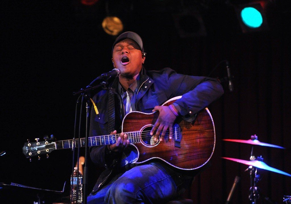 Musician Javier Colon sings and plays guitar while seated