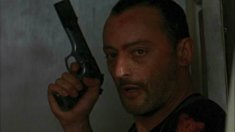 Jean Reno with a gun looking exhausted in Leon The Professional