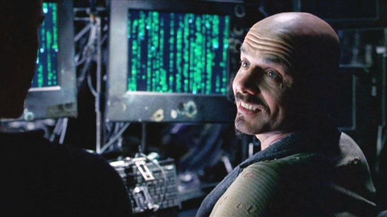 Joe Pantoliano looking over his shoulder and smiling in The Matrix