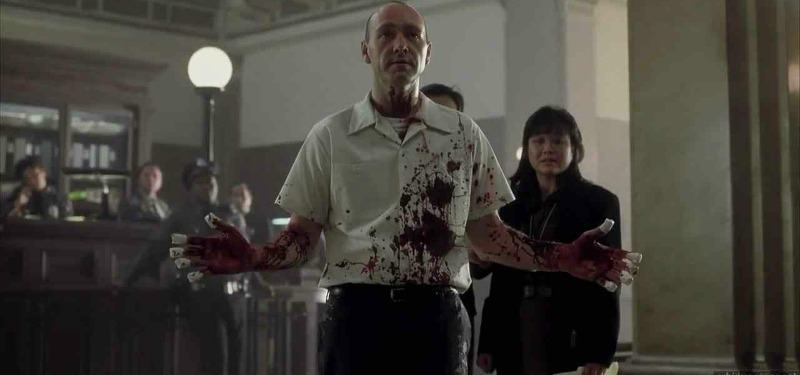 John Doe has his arms up as if to surrender as he is covered in blood.