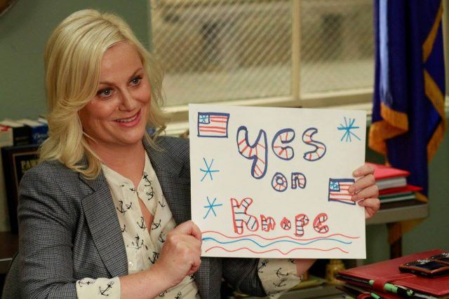 "Leslie Knope holding up a sign that says ""Yes on Knope"""