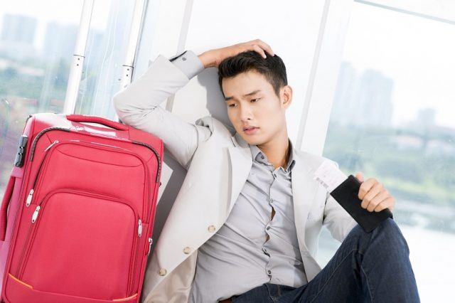 young businessman with luggage in trouble