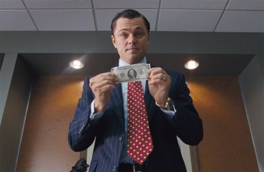 """Celebrity Leonardo Dicaprio holds up a bill in """"The Wolf of Wall Street"""""""