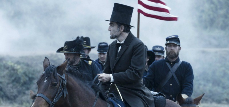 Daniel Day-Lewis as Lincoln on a horse and leading a group of men.