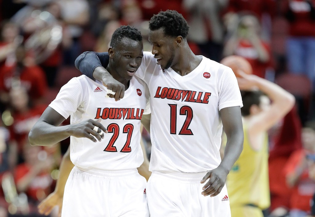Deng Adel #22 and Mangok Mathiang #12 of the Louisville Cardinals celebrate a big win.