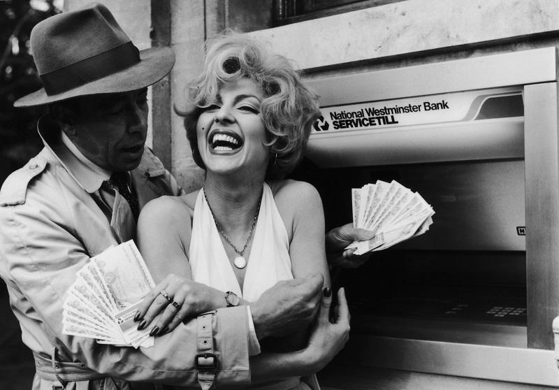 Celebrity lookalikes embrace holding money