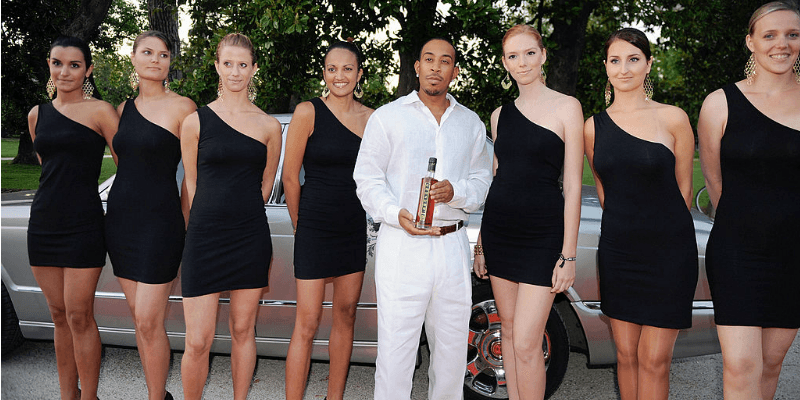 Ludacris posing with women and a bottle of Conjure Cognac