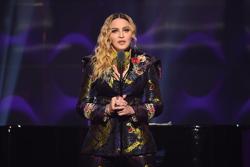 Madonna speaks on stage holding a microphone in front of a black and purple backdrop