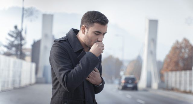 A man coughs while walking down the street.