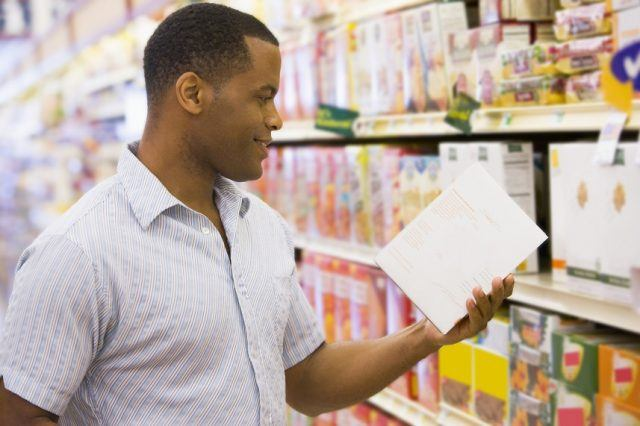 A man picks up and inspects a box of cereal.
