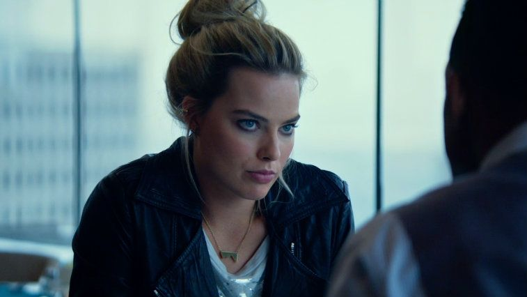 Margot Robbie with her hair up and in a black jacket in the film Focus