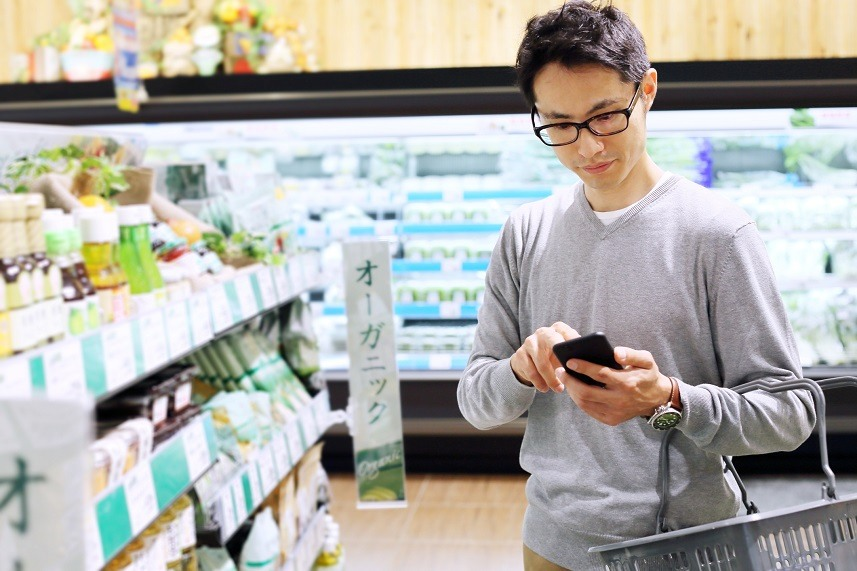 Young man using cellphone in a grocery store