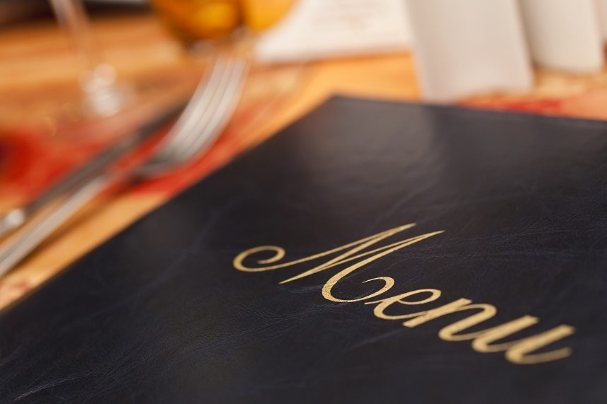 A menu resting on a restaurant table, emphasis placed on the golden embroidery lettering against the black with the image's focus. Silverware, napkins and glasses sit in the background as blurry shapes at the menu's edge, all resting on a light brown table.