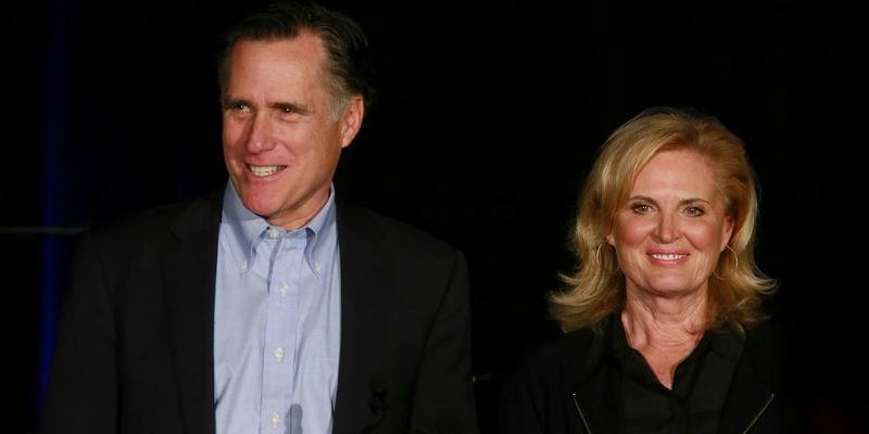 Mitt and Ann Romney are on stage smiling at the crowd.