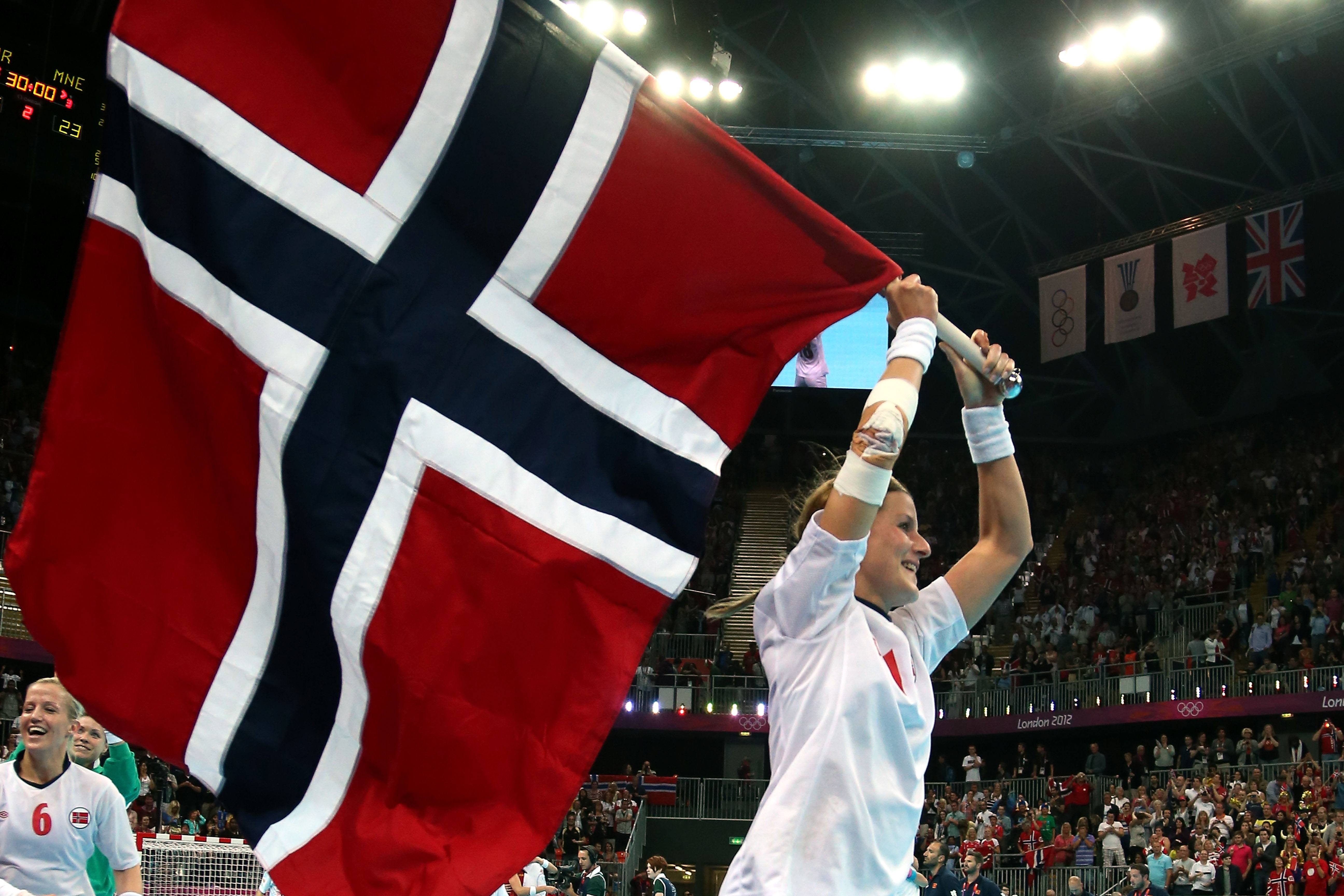 A Norwegian Olympian celebrates with her country's flag