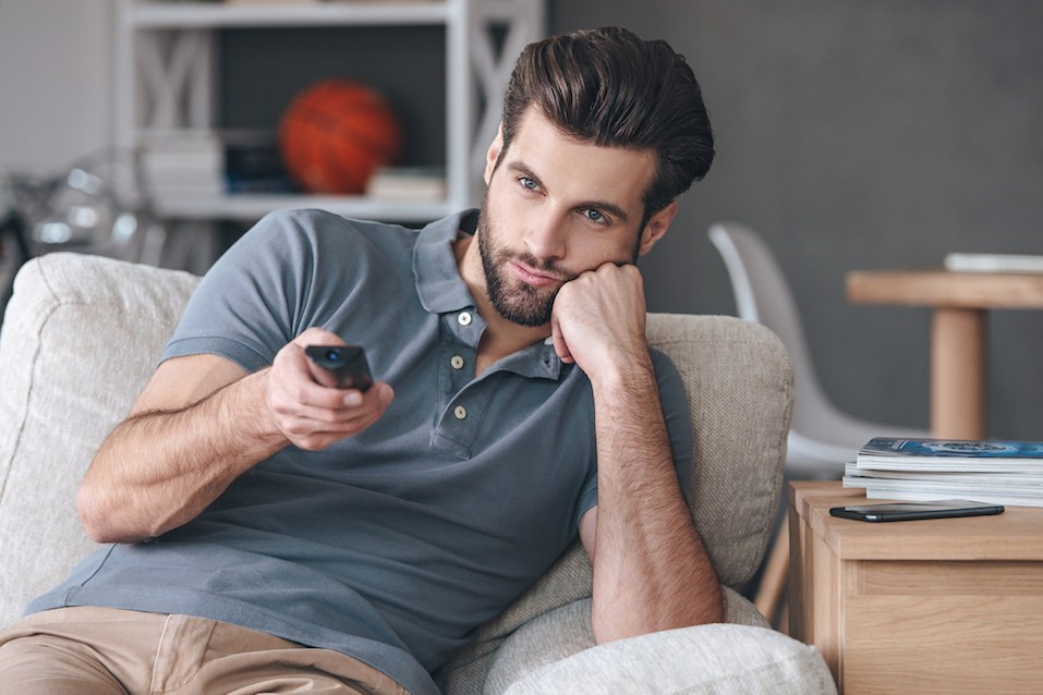 man sitting on couch and watching tv