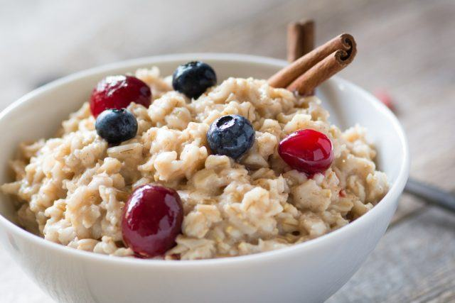 Oatmeal in a bowl with healthy fruit toppings.