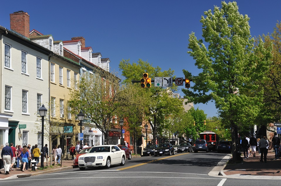 Traffic on KIng Street with people walking on sidewalk along in Old Town Alexandria