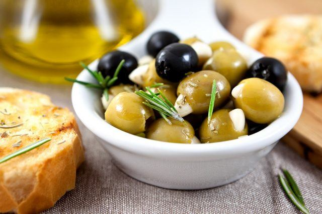 White bowl filled with green and black olives with fresh green herbs on top.