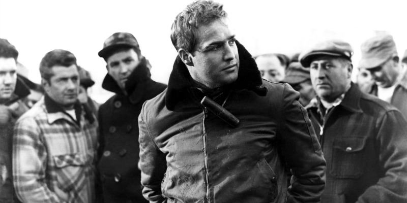 Marlon Brando stands in front of a group of men in On the Waterfront.