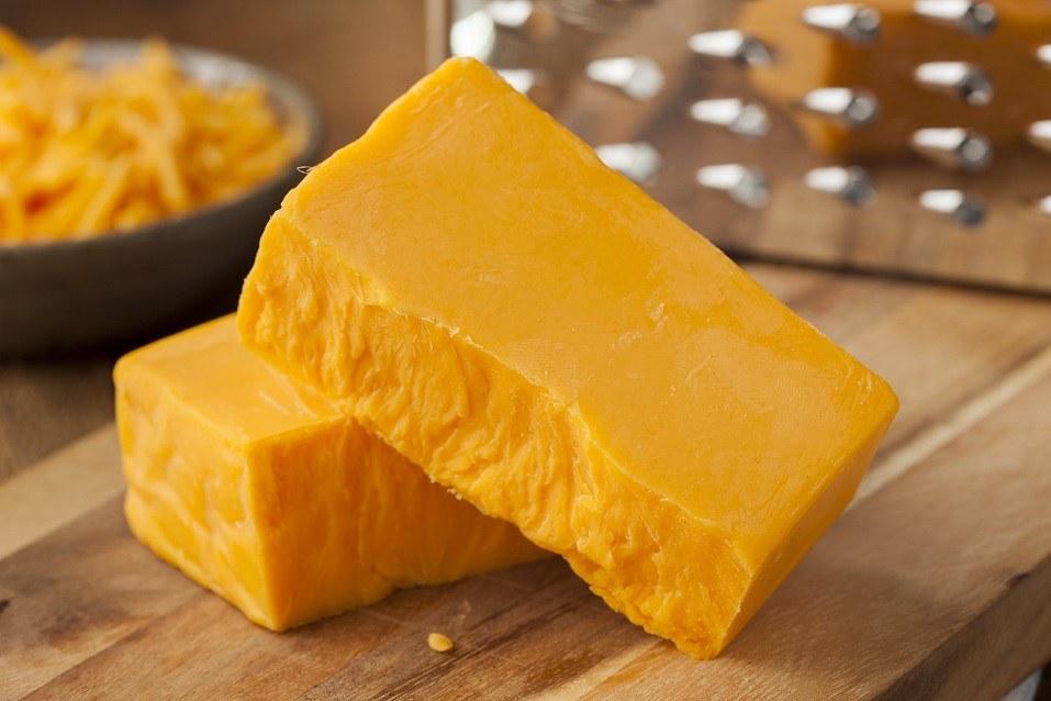 Organic sharp Cheddar cheese on a wooden cutting board.