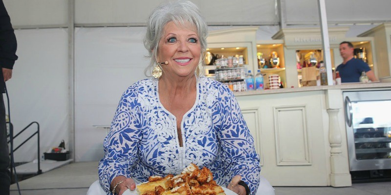 Paula Deen is crouched down holding a plate of food.