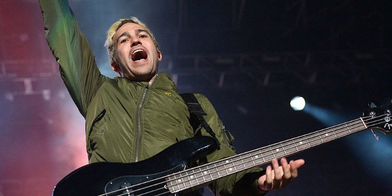 Pete Wentz is playing bass on stage and has one hand in the air.