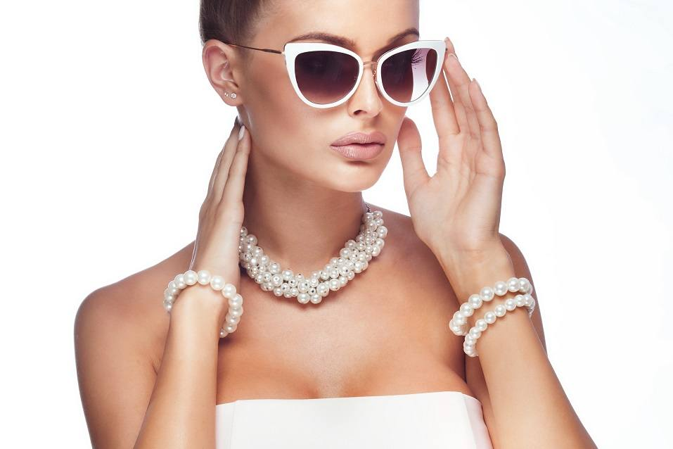 blonde woman wearing pearls and stylish sunglasses