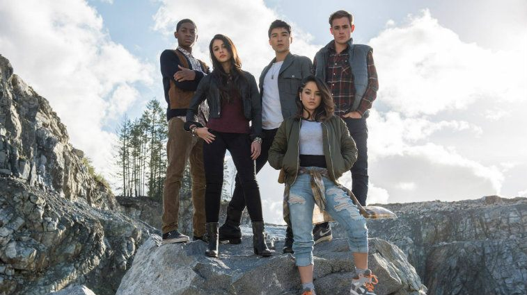 the cast of Power Rangers standing on a rock together