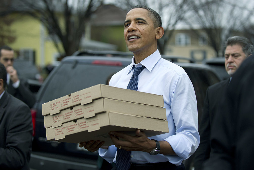President Barack Obama carries boxes of pizza.