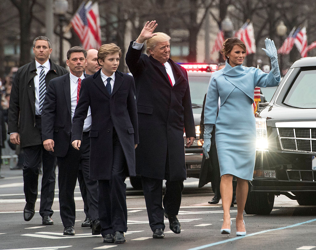 President Donald Trump greets the public during a parade with his son Barron Trump and wife Melania Trump