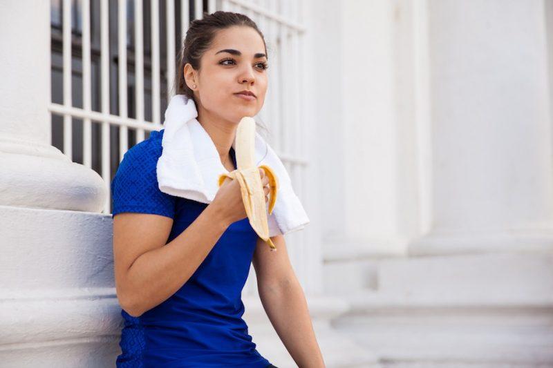 Pretty runner eating a banana