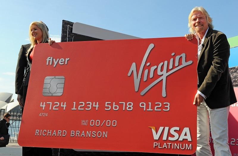 Virgin founder Richard Branson holds a giant Virgin Money credit card.